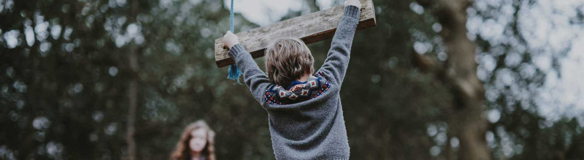 boy in sweater hanging from wooden swing