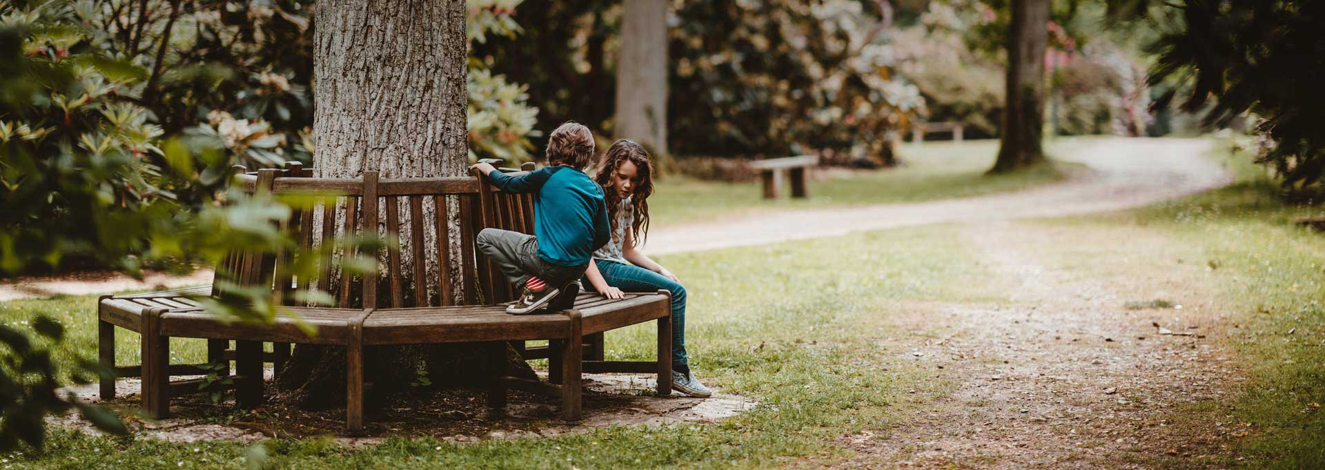 boy and girl sitting on bench surrounding tree in park