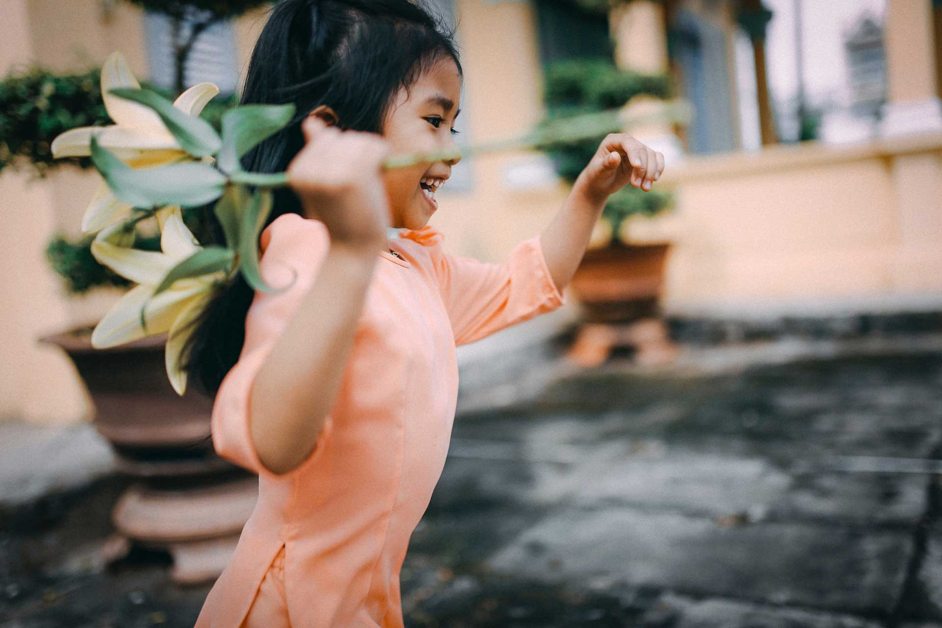 young girl in peach dress running with flower